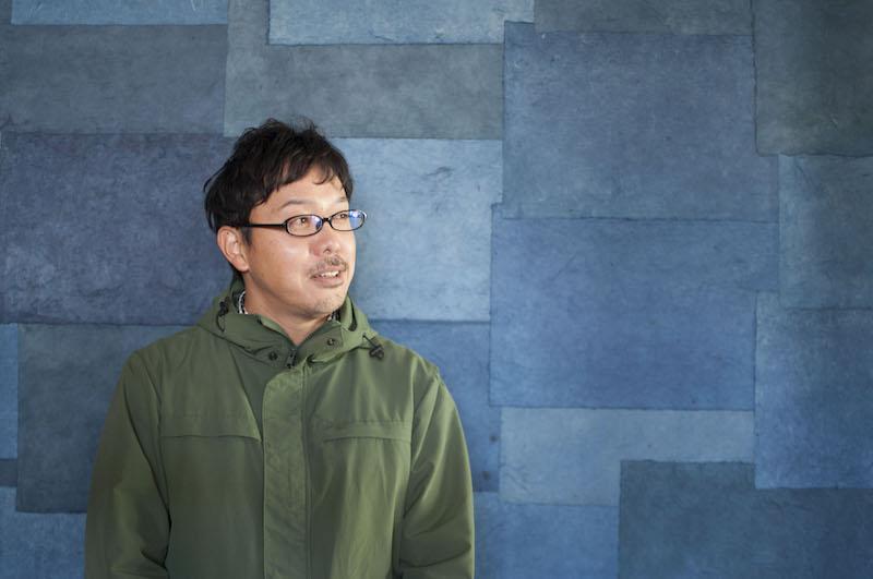 新しいお店『遠近』(おちこち)の、自らが藍で染めた紙の壁の前に立つ東尾さん。実は、壁紙の和紙も楮(こうぞ)から自分で紙すきをして製作している。