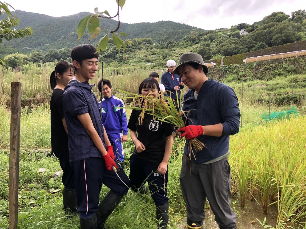 高校生たちが暮らす寮のハウスマスターでもある兼村雅彦さん(右)と寮生たち